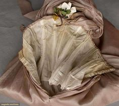 """Augusta Auctions..DIOR COUTURE BALLGOWN, PARIS, S-S 1958..YSL's 1st collection for Dior. Taupe silk, empire bodice, F tie ribbon, white & grey cloth blossoms, strapless w/ back draped scarf, 3-layer bell skirt, white tulle petticoat, built-in corset foundation, labeled """"Printemps-Ete 1958, Christian Dior Paris"""" & stamped """"01?65"""", B 34"""", High W 26"""", CFL 51"""", (3 small holes on skirt front, scattered brown stains, some seams unstitched) very good. Suddon-Cleaver Costume Collection"""