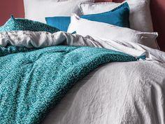 Édredon Mille et une feuilles imprimé d'un motif fleuri bleu canard et vert émeraude contemporain sur fond pétrole. Piquage fantaisie placé, orné de 4 pompons aux extrémités.