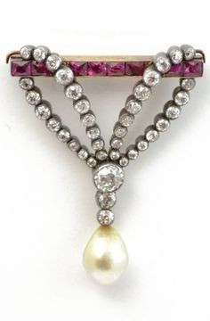 An Antique Ruby, Diamond and Pearl Brooch, Austrian, circa 1890. A brooch set with rubies, diamonds, and a natural pearl drop. The double loop of diamonds, suspended from the ruby bar with a pearl drop. Mounted in silver and gold. #antique #brooch