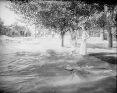 Cherry Creek. Young women wade through Cherry Creek flood waters in Denver, Colorado. The flood was caused by the failure of the Castlewood Dam. Date	1933 :: Western History