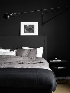 Matte black bedroom with grayscale bedding and framed artwork.