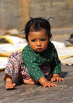 A baby girl in Nepal by herself - and wearing eyeliner-  her eyes speak volumnes. I wish I could pick her up and hold her and if she has no parents, to adopt her and provide her a safe home life..so precious!