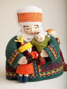"""This scene is typical of everyday rural life in Kyrgyzstan. The dolls are dressed in traditional Kyrgyz clothes, and the woman's coat and head wrap or """"elechek"""" are decorated with traditional Kyrgyz o"""