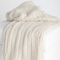 """Cable knit cotton throw in cream.   Product: ThrowConstruction Material: 100% CottonColor: CreamFeatures:  Loose weaveKnitted    Dimensions: 70"""" x 52""""Cleaning and Care: Hand wash with mild detergent and lay flat to dry"""