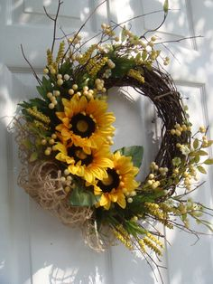 Summer sunflowers, berries and field flowers with a bow made of hemp netting complete this lovely summer wreath. Will add a touch of sunshine