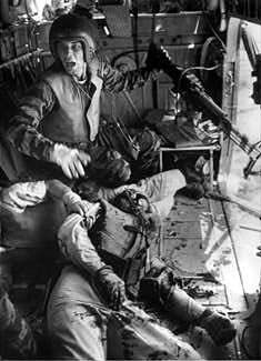 LARRY BURROWS Near Da Nang, Vietnam, 1965    Crew Chief James Farley, with his guns jammed and two wounded comrades aboard, shouts to his gunner. This photo was the LIFE Magazine cover on April 16, 1965.(LIFE/ YP 13)