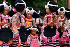 China, Guizhou Province, Longjia village, Long Horn Miao girls in traditional costumes celebrating the Flower Dance Festival, lusheng player. (Bruno Morandi)