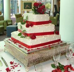Bolo de casamento com fitas e rosas vermelhas. Apoiado em base solida