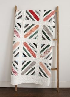 Between The Lines quilt pattern by Denyse Schmidt - love the string piecing with white between each colored piece.