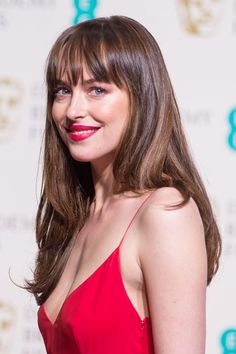 Dakota Johnson matched her lipstick and eye make-up to her scarlet Dior gown, leaving her hair loose | BAFTA 2016 | Vogue UK
