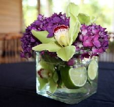 what an adorable mini arrangement of limes, cymbidium orchids and some unidentified purple flowers :)