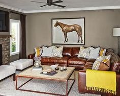 A thick, natural fiber rug grounds the seating area in this transitional living room. A rustic-industrial coffee table is paired with a comfy leather sectional, creating a nice mix of textures that reflects the home's setting. Bursts of yellow in the accessories add interest and further the room's ties with its sunny surroundings.