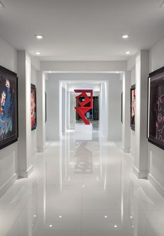 "A veritable art gallery, this hallway dazzles with six ""Myths Series"" screen prints by pop artist Andy Warhol. Welded and painted Ferrari red, the industrial sculpture designed by homeowner Adrienne Krieger stands out like a cherry on a sundae."