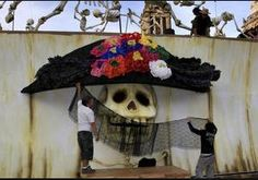 "In this Wednesday, Oct. 30, 2013 photo, artists decorate a traditional Mexican ""Catrina"" as part of the Day of the Dead celebrations in Mexico City's main plaza, the Zocalo. Mexico City is marking the 100th anniversary of the death of the artist who first drew the elegant skeleton lady known as the""Catrina."" The figure was first done as a satirical engraving by artist Jose Guadalupe Posada somewhere between 1910 and his death on Jan. 20, 1913."