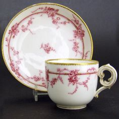 An 18th Century Sevres Porcelain Cup and Saucer, 1756. Decorated in Puce with Meandering Lose Garlands of Roses Intertwining a Ribbon. The Handel of Rococo Form. The Base with Interlaced L's for the Sevres Porcelain Factory and 'D' for 1756. The Top of the Sevres Mark has a Painter's Mark that I have not been Able to Identify.