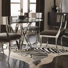 Sleek modern dining table and chair set with round glass table top sits above a bold polished stainless steel pedestal base.