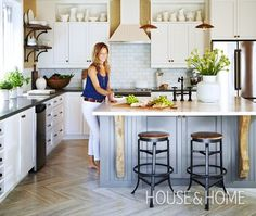 A herringbone-patterned travertine floor, along with grasscloth wallpaper by Thibaut and a wood-panelled ceiling, bring texture and character to this room. The kitchen got a new lease on life with the addition of Ikea base cabinets fitted with custom doors to match the existing uppers. The marble-topped island was painted a contrasting grey and a $300 range hood in beadboard was painted a creamy white to match the cabinets.