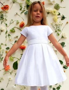 Elegant and understated, the clean lines of this gorgeous girls special occasion dress compliment all events: Flower Girl, Communion, Birthdays, Cotillion, Recitals and Father Daughter Dances. Its cap sleeve bodice has a boat neck cut and back of cascading covered buttons (concealing a comfortable zipper). A closer look reveals box pleats and a removable pleated sash. Dress is available at the knee as a party dress or mid-calf for more formal events.