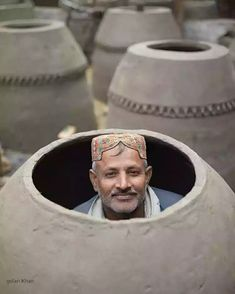 A man sits inside ovan these ovens are used to back wheat and are common all around Pakistan, Lahore Punjab Pakistan