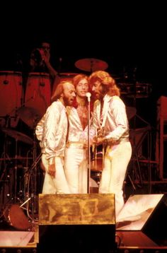 NEW YORK - SEPTEMBER 7: Maurice Gibb, Robin Gibb and Barry Gibb of The Bee Gees harmonising around a microphone while performing on stage at Madison Square Garden on the Spirits Having Flown Tour on September 7th, 1979 in New York.