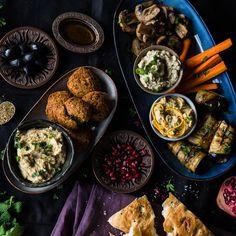 Es schmiegen sich knusprige Falafel an cremigen Hummus-Variationen und Baba Ghanoush. Dazu gibt es gebratene Champignons, Auberginenröllchen und Oliven.
