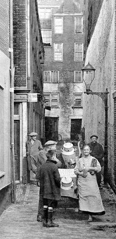 """Op de Veemarktdagen, begin jaren 1930, trok er een vrouwtje door de stad met een klein karretje, dat ze achter zich aantrok met twee melkbussen erin. Ze molk de koeien op de Veemarkt die teveel melk in hun uiers hadden. Die melk verkocht ze als """"marrrrtmellek"""" en daar verdiende ze haar geld mee. Soms had ze biest, dat is de eerste melk van een koe nadat ze heeft gekalfd. Hier brengt ze haar waar aan de man in de Bellegang, een steegje op de Schiedamschedijk."""