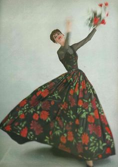 Anne St. Marie wearing a black silk dress printed with giant roses and its little top passes behind a cloud of chiffon, by James Galanos, May 1957