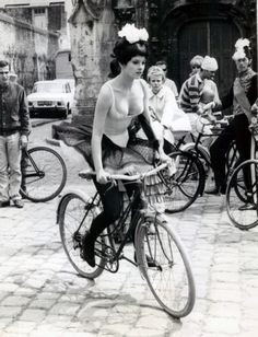 I love everything about this image. The gorgeous bike, black and white photography, beautiful slender figure of the lady and pretty face, costume including everyone else's, buildings.