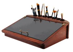 Craftech Artisan Tabletop Painting Desk  Model A-204    Tempered glass top offers a vast surface for mixing paint  Stylish brush holder to store a large quantity of brushes  Compartment under the lid provides ample room for storing paint tubes or painting mediums  The glass is hinged allowing the artist to change backgrounds and view reference material    Dimensions:  24in x 20in x 7in