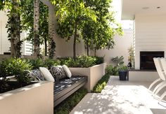 A creative solution to bench seating and garden design in this alfresco combining mirrors with the landscaping. Photo credit: swellhomes.com.au