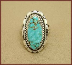 """Very beautiful, this handmade sterling silver ring is made and signed by Navajo artist Larry Yazzie. It is set with a Number 8 Turquoise gemstone (mined in Nevada) that is a light aqua-green with webbed light brown matrix. The stone is set in a smooth bezel housing surrounded by twisted silver rope and traditional Navajo designs. The ring measures 1.17"""" long and 0.68"""" wide at the widest area"""