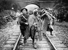 Controversial Topics: THE WESTERN FRONT: A CENTURY LATER - A German prisoner, wounded and muddy, helped by a British soldier along a railway track. A man, possibly in French military uniform, is shown behind them, holding a camera and tripod, ca. 1916. (National Library of Scotland) #