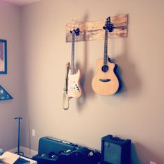 guitars hanging on the wall to save space possible on a piece of metal or wood