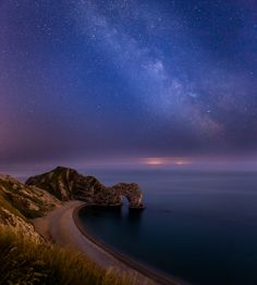 """500px / Milky Way over Durdle Door by Damian Garcia. """"Photo of the Milky Way over Durdle Door [Dorset coast, UK]. The lights in the distance are coming from northern France, which is 60 miles away. Just goes to show how far light pollution travels!"""""""