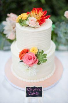 Buttercream-frosted wedding cake adorned by bright florals. | Photo by Petula Pea Photography, Second Shooter: Katie Beverley, Cake by Elizabethan Desserts