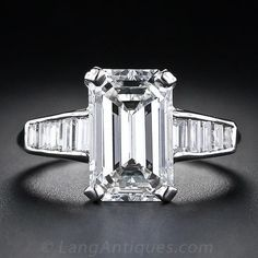 A bright-white, radiant and classically proportioned emerald-cut diamond, weighing 3.18 carats, glistens from between two rows of shimmering baguette diamonds in this breathtakingly beautiful estate engagement ring, hand fabricated in platinum, circa 1950s. The diamond is accompanied by a GIA - Gem Trade Laboratory - grading report stating: H color - VS1 clarity. A magnificent and timeless estate diamond ring.