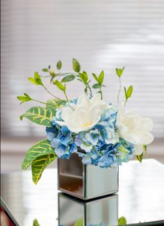 The delicate white real touch Plumeria is popular in tropical or beach wedding bouquets for its graceful flowers and bright colour. This arrangement is placed into mirror square vase with light blue hydrangeas to insure to bring a pop of colour into any home. Height: 18 cm