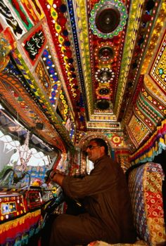 Pakistan, colorfully decorated truck interior, driver at wheel