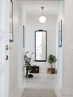 Narrow corridor painted white with white floors and monochrome details Narrow Hallway Decorating, Foyer Decorating, Hallway Inspiration, Interior Inspiration, Feng Shui Dicas, Hallway Walls, Long Hallway, White Hallway, Flur Design
