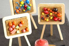 Fun candy canvas art project created with graham crackers, Skittles, M's, Starburst, frosting, and small easels from a craft store.