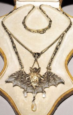 An Art Nouveau 'Bat' necklace, attributed to Lucien Janvier, circa 1900. Composed of silver, silver gilt, plique-à-jour enamel and pearls.