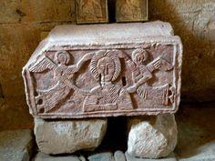 Capitel suelto con figura de mujer. Entre dos ángeles, con una mano en el pecho, estaría situado en el arco que existiría entre la nave central y la de crucero.