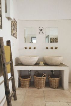 Rustic stone floor and basins with wooden ladder for hanging towels and linens - bathroom design