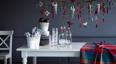 Christmas decorations hanging over a dining table with plates, glasses, cutlery and bottles