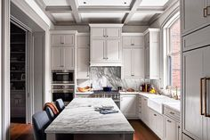 Seeking a quiet look for this historic Philadelphia townhouse's kitchen, which is visible from the dining room and hallway, designer Ashli Mizell employed statuary marble slabs on the countertops, island, and backsplash. The refrigerator is masked by paneled cabinetry.