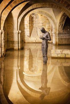 fuckinmiki:    Flooded crypt of Winchester Cathedral A calm space under Winchester Cathedral - Antony Gormley's statuePhotograph:Tycho1234/GuardianWitness
