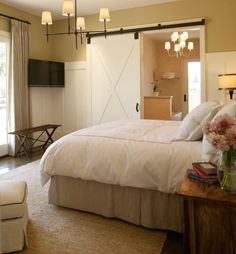 Beautiful bedroom with sliding barn door, yellow walls paint color, TV, taupe pinch-pleat curtains, seagrass rug, Bryant Chandelier in Bronze, white hotel bedding with gold stitching, gray bed skirt and wood nightstands. by Annc7