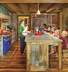 Rustic Cabin Kitchen    This family kitchen in Charlottesville, Virginia, looks like the workspace in a rustic log cabin, only with modern appliances. The large beams and cabinet fronts are made of wormy chestnut barn siding. Iron hardware made by a local craftsman is used throughout the space.