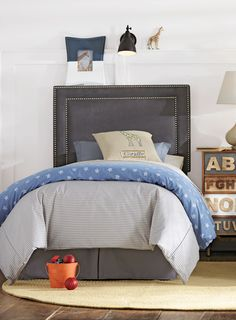 A nailhead-trimmed custom headboard ties this whole look together. Perfect for your little boy. HomeDecorators.com #kids