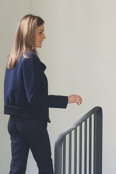 Queen Letizia wore a Nina Ricci navy/black bomber-style wool jacket from the Pre-Fall 2014 Collection over a lavender Hugo Boss 'Banora' silk blouse which she also owns in vanilla white. She carried a pair of Ray-Ban aviator sunglasses tucked into her blouse.